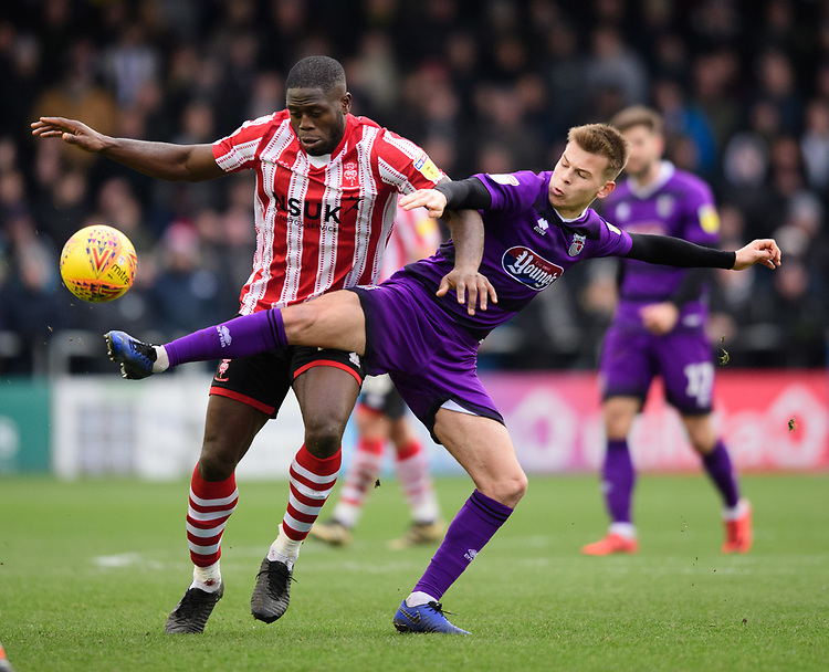 Lincoln City's John Akinde vies for possession with Grimsby Town's Jake Hessenthaler<br /> <br /> Photographer Chris Vaughan/CameraSport<br /> <br /> The EFL Sky Bet League Two - Lincoln City v Grimsby Town - Saturday 19 January 2019 - Sincil Bank - Lincoln<br /> <br /> World Copyright &copy; 2019 CameraSport. All rights reserved. 43 Linden Ave. Countesthorpe. Leicester. England. LE8 5PG - Tel: +44 (0) 116 277 4147 - admin@camerasport.com - www.camerasport.com