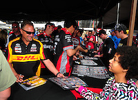 Mar. 10, 2012; Gainesville, FL, USA; NHRA funny car driver Jeff Arend (left) signs autographs and greets fans during qualifying for the Gatornationals at Auto Plus Raceway at Gainesville. Mandatory Credit: Mark J. Rebilas-