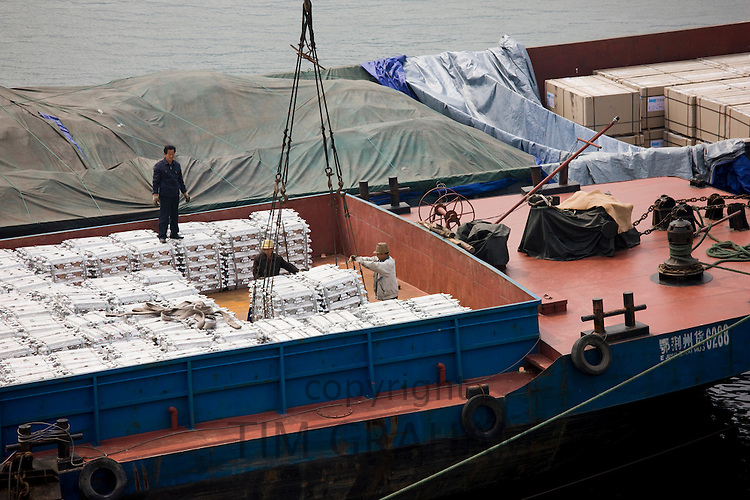 Aluminim ingot blocks being loaded onto cargo ship, Yichang, China
