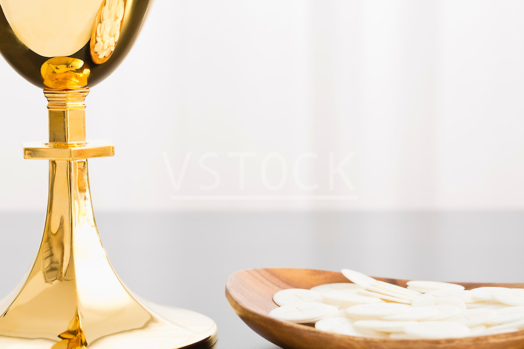 Christian holy communion, gold chalice and communion wafer on plate