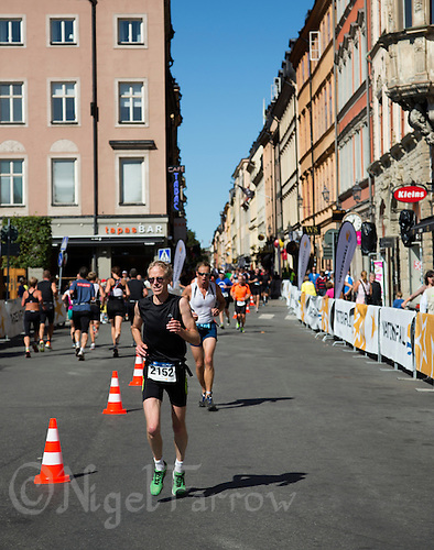 25 AUG 2013 - STOCKHOLM, SWE - A competitor runs through the streets of Gamla Stan during the Stockholm Triathlon in Stockholm, Sweden (PHOTO COPYRIGHT © 2013 NIGEL FARROW, ALL RIGHTS RESERVED)