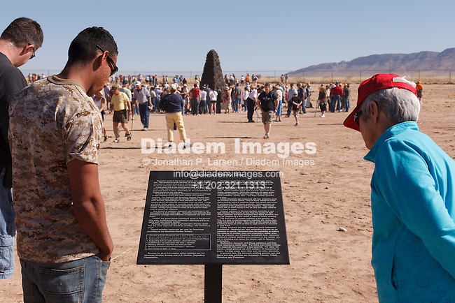 Sightseers read a sign at Trinity Site in New Mexico describing radiation at the the site.  Trinity Site, marked by an obelisk in the background, is where the the world's first nuclear device was exploded in 1945.