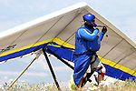 A hang glider pilot checking his equipment prior to lanunching into world famous Chelan air from Chelan Butte in eastern Washington, USA