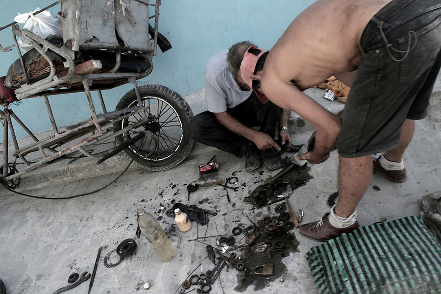 Havana (Cuba). September 2006..La Habana Vieja. Repairing a bicycle-taxi.