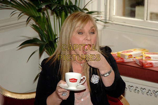 HELEN LEDERER.Mr Kipling National Gossip Survey press launch & photocall, 68 Dean Street, London, UK..March 14th, 2006.Ref: PL.half length mug sweet food cup saucer tea eating.www.capitalpictures.com.sales@capitalpictures.com.©Capital Pictures