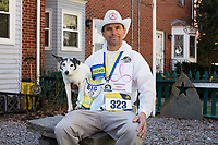 Carlos Arredondo, 57, sits with his dog, Buddy, in their front yard in Roslindale, Boston, Massachusetts, USA, on Sat., March 31, 2018. Arredondo is well known as the &quot;man in the cowboy hat&quot; who helped out in the aftermath of the Boston Marathon Bombing in 2013. Carlos is wearing a jacket that he has used to create a t-shirt design for when he runs the Boston Marathon later this year. Though he has run the race unofficially previously, this will be the first time he runs it &quot;legally,&quot; he says.<br /> <br /> Behind the Carlos is a memorial to his two sons,  Marine Lance Corporal Alexander Scott Arredondo and Brian Arredondo. Alex was killed while serving in Iraq in 2004, and Brian died by suicide in 2011. <br /> <br /> Carlos says he often accidentally calls Buddy by his son's name, Brian. Brian Arredondo died by suicide in 2011 after a battle with depression following the 2004 death of Arrendondo's other son Marine Lance Corporal Alexander Scott Arredondo, who was killed while serving in Iraq.