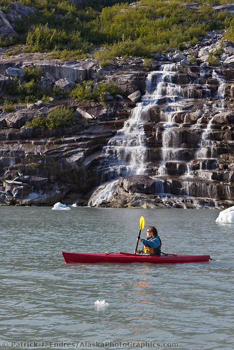 Tourists kayak amongst icebergs and waterfall in  Western Chugach National Forest, Kenai Peninsula, Prince William Sound, southcentral, Alaska.