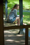 Young woman sitting on porch, photographed through screen door