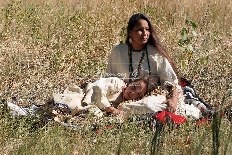 A Native American Sioux Indian mother and daughter sitting on a blanket in the grasses of South Dakota
