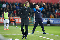 (L-R) Graham Potter, manager for Swansea City and Paul Cook, manager for Wigan Athletic react on the touch line during the Sky Bet Championship match between Swansea City and Wigan Athletic at the Liberty Stadium, Swansea, Wales, UK. Saturday 29 December 2018