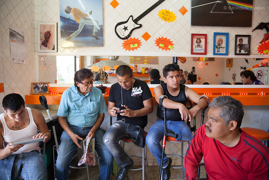 """Players from Guerreros Aztecas meet for lunch at a burger's restaurant in Mexico City, Mexico on July 27 2014. Guerreros Aztecas (""""Aztec Warriors"""") is Mexico City's first amputee football team. Founded in July 2013 by five volunteers, they now have 23 players, seven of them have made the national team's shortlist to represent Mexico at this year's Amputee Soccer World Cup in Sinaloathis December.The team trains twice a week for weekend games with other teams. No prostheses are used, so field players missing a lower extremity can only play using crutches. Those missing an upper extremity play as goalkeepers. The teams play six per side with unlimited substitutions. Each half lasts 25 minutes. The causes of the amputations range from accidents to medical interventions – none of which have stopped the Guerreros Aztecas from continuing to play. The players' age, backgrounds and professions cover the full sweep of Mexican society, and they are united by the will to keep their heads held high in a country where discrimination against the disabled remains widespread.(Photo byBénédicte Desrus)"""