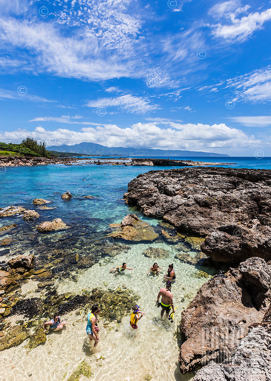 Tourists on the beach at Shark's Cove on the North Shore of O'ahu.