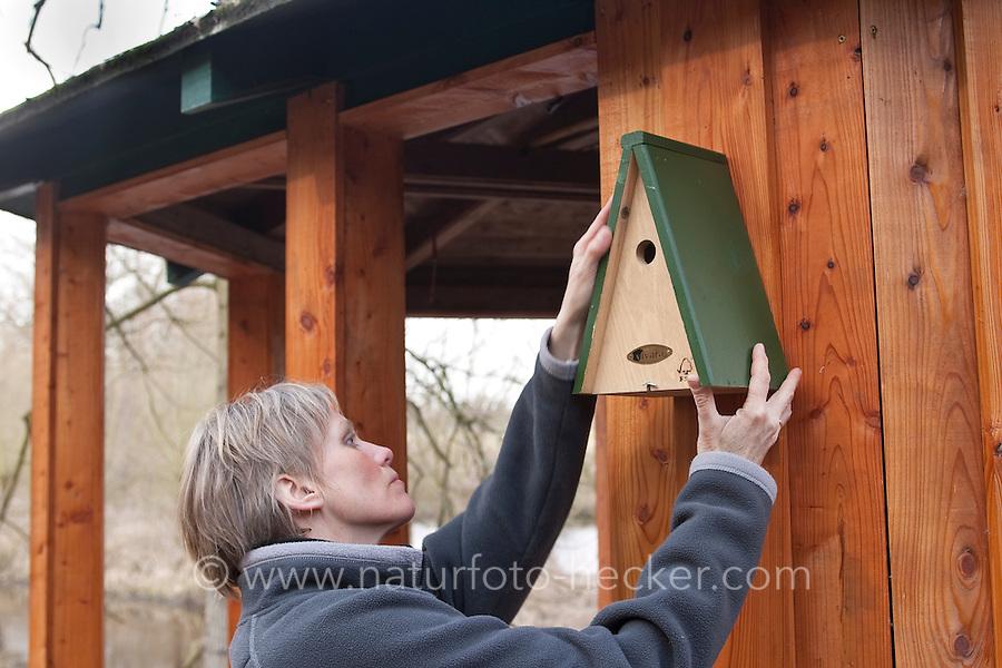 Frau hängt einen Nistkasten für Vögel auf, Meisenkasten, Vogelnistkasten