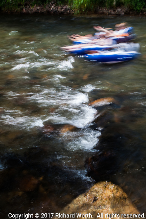 Slow shutter blur accentuates the motion of blue and white tubes, and their occupants, racing down Clear Creek in the Rocky Mountain foothills, Golden, Colorado.
