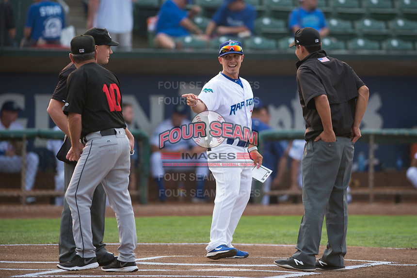 Ogden Raptors manager Jeremy Rodriguez (7) meets with Great Falls Voyagers manager Tim Esmay (10) and umpires Bobby Tassone (left) and Rene Gallegos before a Pioneer League game against the Great Falls Voyagers at Lindquist Field on August 23, 2018 in Ogden, Utah. The Ogden Raptors defeated the Great Falls Voyagers by a score of 8-7. (Zachary Lucy/Four Seam Images)