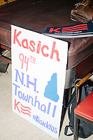 "A handwritten sign reads ""Kasich 94th NH Townhall"" while Ohio governor and Republican presidential candidate John Kasich speaks at a town hall campaign event at Raymond VFW Post 4479 in Raymond, New Hampshire, on Wed., Feb. 3, 2016."