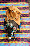 A man on a donkey standing on a colorful carpet, Essaouira, Morocco