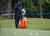 19.05.2015. Wentworth, England. BMW PGA Golf Championship. Practice Day.  Joost Luiten's caddie practices his swing with an umbrella during the practice round of the 2015 BMW PGA Championship from The West Course Wentworth Golf Club