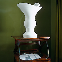 A contemporary plaster vase stands on top of an antique washstand in a corner of the master bedroom