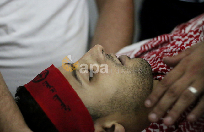Palestinian relatives mourn over the body of 27-year-old Moataz Zawahra, who was killed by Israeli security forces in the clashes with Palestinian protesters, at a hospital morgue in the West Bank city of Bethlehem, October 13, 2015. A wave of stabbings that hit Israel, Jerusalem and the West Bank this month along with violent protests in annexed east Jerusalem and the occupied West Bank, has led to warnings that a full-scale Palestinian uprising, or third intifada, could erupt. The unrest has also spread to the Gaza Strip, with clashes along the border in recent days leaving nine Palestinians dead from Israeli fire. Photo by Muhesen Amren