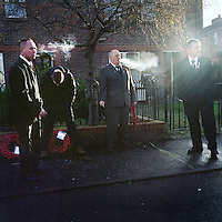 Paul, Tommy (centre) and Graeme standing by a set of wreaths and smoking at a Remembrance Sunday service for the North Belfast battalion of the Ulster Defence Association (UDA) at Tigers Bay estate, a loyalist part of Belfast. The names of UDA members who were killed in 'The Troubles' (a period of intercommunal violence and strife which lasted for approximately 3 decades from the 1960s to 1998, when the Good Friday Agreement ended outright hostilities) are read aloud with wreaths and crosses placed by family and friends...