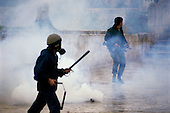 Jerusalem, Israel<br /> January 15, 1988<br /> <br /> Israeli soldiers move into the Dome of the Rock as Palestinians shout anti-Israeli slogans and burn Israeli and American flags after Friday ceremonies. Israel soldiers shoot tear gas into the Dome as young Palestinians throw rocks at the soldiers. Several police and at least 70 Palestinians are injured as the Israelis beat Palestinians with clubs during the 1 hour ordeal.