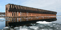 A late-spring view of the Lower Harbor Ore Dock reflecting in the icy Lake Superior water. Marquette, MI