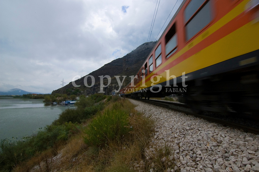Red-yellow train sweeps away next to the Unesco protected Skadar lake in Montenegro, Europe