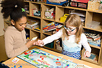 Public school grade 2 two girls playing Monopoly board game during choice time horizontal