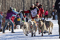 XXX and team run past spectators on the bike/ski trail during the Anchorage ceremonial start during the 2014 Iditarod race.<br /> Photo by Britt Coon/IditarodPhotos.com