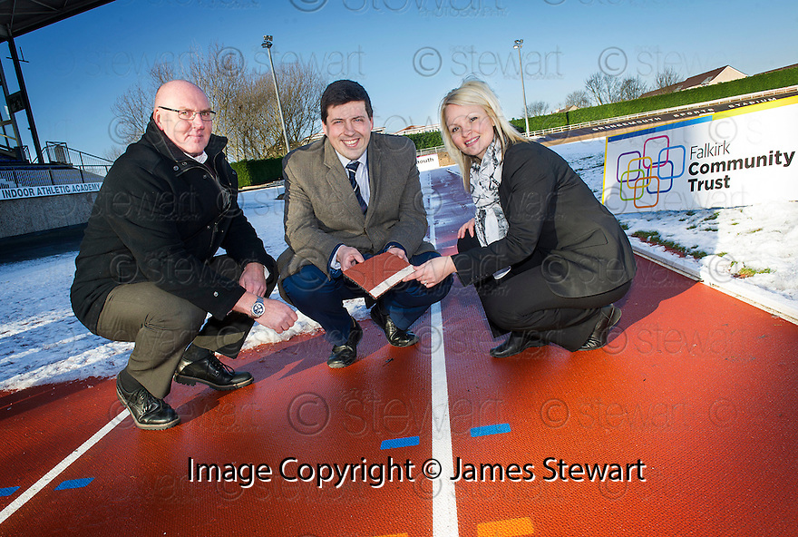Jamie Hepburn MSP, Minister for Sport, Health Improvement and Mental Health (centre) is shown the former Commonwealth Games track laid at Grangemouth Stadium by Brian Pennycook, Team Leader Sport and Leisure and Natalie Sreenan, Duty Officer.