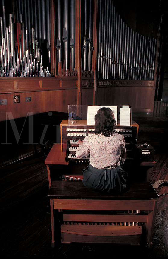 Pipe organ, a female organist sits at the keys with her back to the camera.  May not be used in an elementary school dictionary. Cleveland Ohio USA.