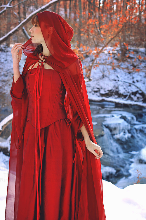 A young brunette female wearing a mysterious red hooded dress in front of a pretty waterfall gazes away sadly