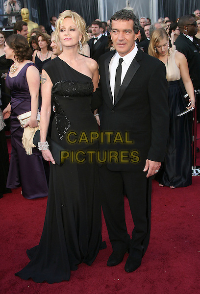 Melanie Griffith, Antonio Banderas.84th Annual Academy Awards held at the Hollywood & Highland Center, Hollywood, California, USA..February 26th, 2012.oscars full length black dress one shoulder clutch bag tattoo suit married husband wife .CAP/ADM.©AdMedia/Capital Pictures.