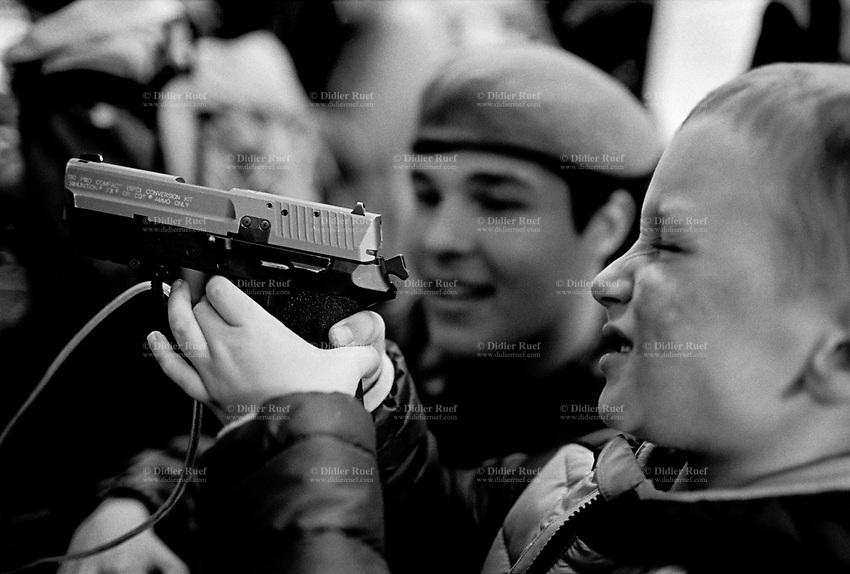 "Switzerland. Canton Bern. Thun. A young boy plays with a SIG Sauer Pro series pistol at the swiss army stall during the military event ""Thun meets Army & Air Force"". The SIG Pro is a series of semi-automatic pistols developed and manufactured jointly by Schweizerische Industrie Gesellschaft (SIG) and J. P. Sauer & Sohn. It was the first polymer-frame handgun from either company and one of the first pistols to feature a built-in universal accessory rail and interchangeable grips. The SIG Pro is a short recoil operated, locked breech semi-automatic pistol. It uses a traditional Browning cam-operated locking system. The barrel locks into the slide via enlarged ejection port. 21.10.2016 © 2016 Didier Ruef"