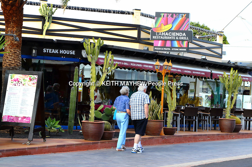 LANZAROTE, CANARY ISLANDS - Tourists pass a restaurant in the beach resort of Costa Teguise during January 2016 in Lanzarote, Canary Islands<br /> <br /> Photo by Keith Mayhew