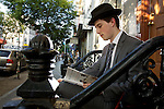 A well dressed man sits on some steps in Williamsburg, NY smoking a cigarette and reading a book by Bill Bryson. He wears a grey suit and a fedora hat.