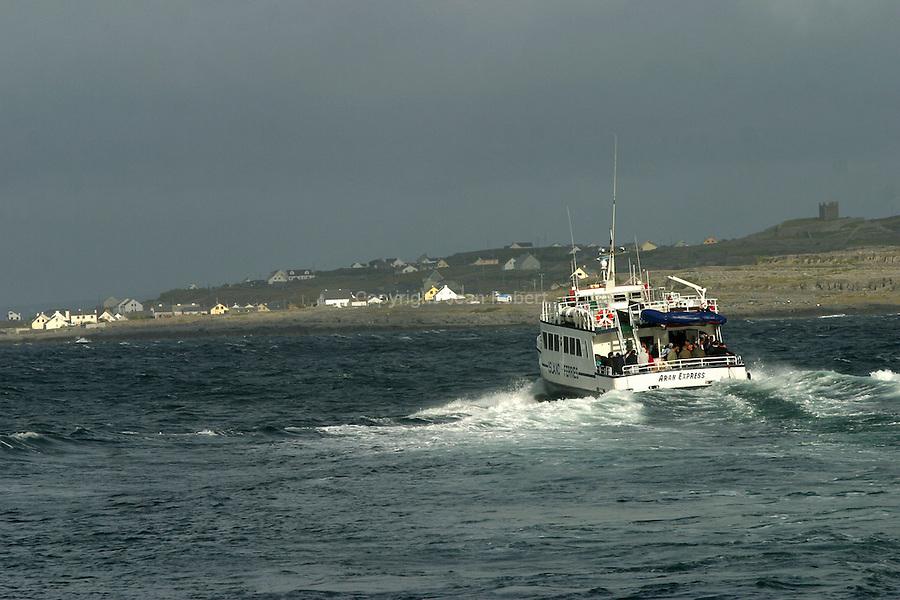 navette maritime (Aran express) reliant la côte de Galway à l'île d'Inishmaan. Débarquement des passagers et du fret sur la jetée d'inishmaan en fin de soirée. ïle d'Inisheer au fond.boat ((Aran express) sailinfg from the coast of Galway to Inishmaan island. Pier of Inishmaan