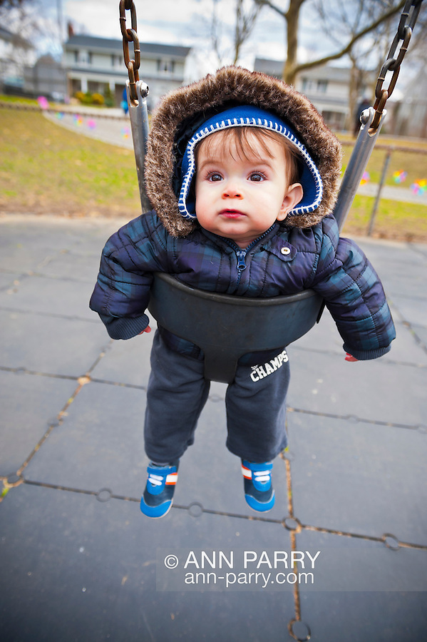 March, 23, 2013 - Merrick, New York, U.S. - RYAN M, 10 months old, is one of the young children swinging on swing after the Egg Hunt at the Annual Eggstravaganza at Fraser Park. He wore a coat because of windy, unseasonably cold weather for spring.