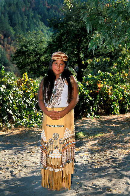 Full shot of a traditional Yurok girl; (11yrs old); poses in a traditional leather skirt decorated with shells; seeds and woven grass. Jene also is wearing traditional beaded shell necklaces and a basket woven hat. Hoopa Valley Indian Reservation; California