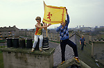 Young kids hold the Scottish flag above their heads from the roof tops of a huge council block of flats Blackhill estate Glasgow 1980s  Teens playing truant.