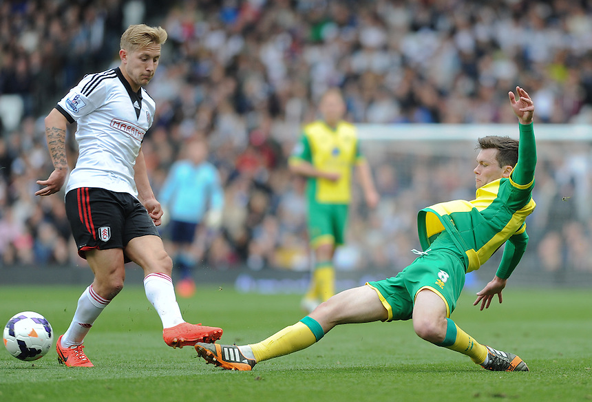Fulham's Lewis Holtby is tackled by Norwich City's Jonathan Howson<br /> <br /> Photo by Ashley Western/CameraSport<br /> <br /> Football - Barclays Premiership - Fulham v Norwich City - Saturday 12th April 2014 - Craven Cottage - London<br /> <br /> &copy; CameraSport - 43 Linden Ave. Countesthorpe. Leicester. England. LE8 5PG - Tel: +44 (0) 116 277 4147 - admin@camerasport.com - www.camerasport.com