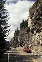 AJ3699, Mount Rainier, scenic road, Mount Rainier National Park, Cascades, Cascade Range, Washington, Red car approaches a tunnel on the Stevens Canyon Road at Mount Rainier National Park in the state of Washington.