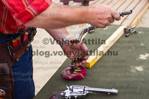 Participant unloads his revolver after his competition during the Cowboy Action Shooting European Championship in Dabas, Hungary on August 11, 2012. ATTILA VOLGYI