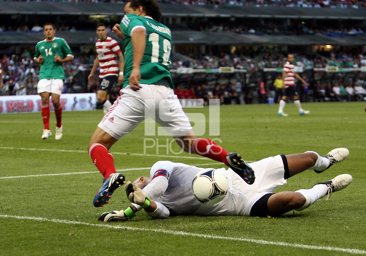 MEXICO CITY, MEXICO - AUGUST 15, 2012:  Tim Howard (1) of the USA MNT smothers the ball at the feet of Andres Guardado (18) of  Mexico during an international friendly match at Azteca Stadium, in Mexico City, Mexico on August 15. USA won 1-0.