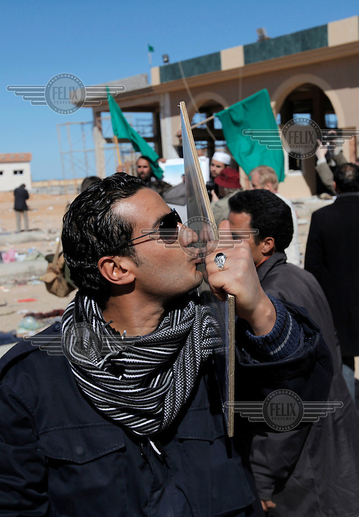 A man kiss a picture of Col. Gadaffi. Suddenly, in the afternoon of March 2, there was no more refugees coming across the border from Libya into Tunisa. Libyan police put on a PR stunt for the press, handing over food and water to the last refugees to go. Then telling the press all is well in Libya. ..Tens of thousands of people, mainly Egyptian workers, fled unrest in Libya and crossed the border into Tunisia. Some slept in the open for several days before being processed.  At the same time forces loyal to Col. Gaddafi fought opposition forces in various parts of the country.