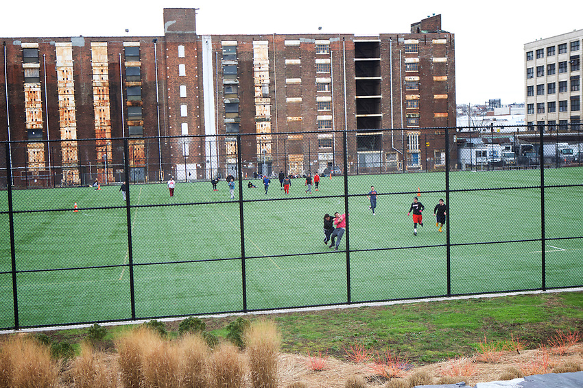 BROOKLYN, NY - JANUARY 17, 2016:  Playing football in the sports fields at Bush Terminal Park, which opened in November 2014.<br /> LOCATION: Bush Terminal Park, The Waterfront, between 43rd Street and 51st Street.<br /> CREDIT: Clay Williams for the New York Times.<br /> <br /> &copy; Clay Williams / claywilliamsphoto.com