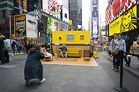 "Tourists pose for photographs in #SetintheStreet, an interactive film set in the middle of Times Square in New York on Friday, April 17, 2015. Created by Justin Bettman, the public art project made out of found items allows visitors to pose for photos in a ""film still"". The project in Times Square is in collaboration with the Tribeca Film Festival. Between uses found materials and hopes that #SetintheStreet will cause people to re-evaluate their thinking about trash.  (© Richard B. Levine)"