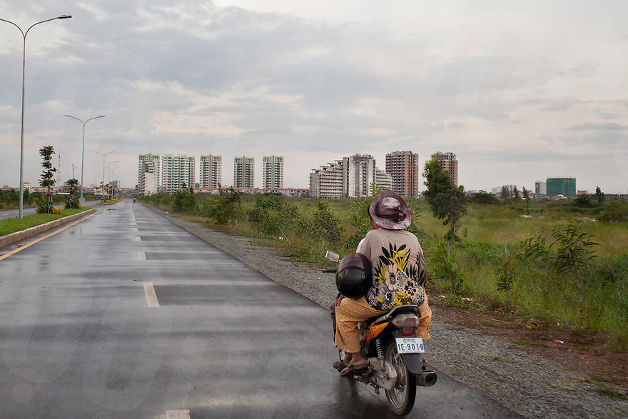 July 27, 2012 - Phnom Penh, Cambodia. A couple drive towards Camko city on the outskirts of Phnom Penh. Camko is a gated multi-housing complex.