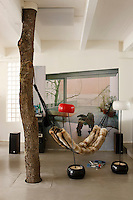 In this corner of the living room trompe l'oeil wallpaper hides the guest bathroom and gives the feeling of an outdoor space, heightened by an oak tree trunk used to support a hammock